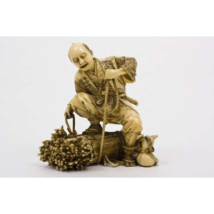Ivory figure of a man tying a bundle of wood
